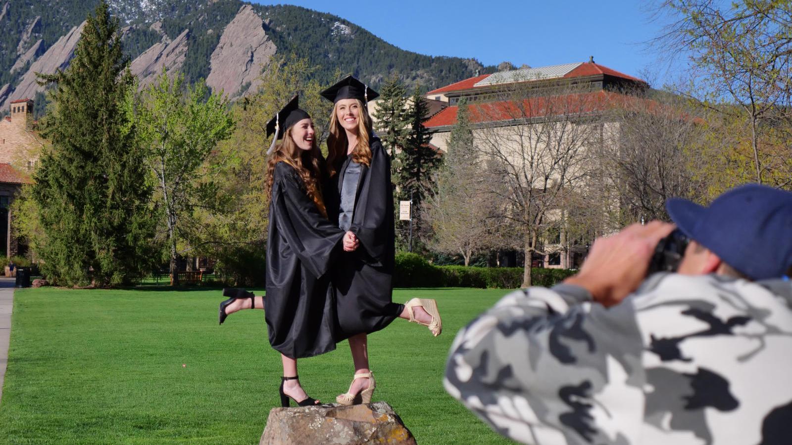 graduates on rocks in front of Flatirons
