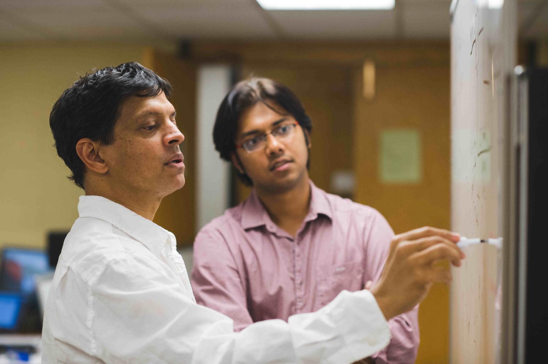 Prof. Mahesh Varanasi and student discuss research in the lab.