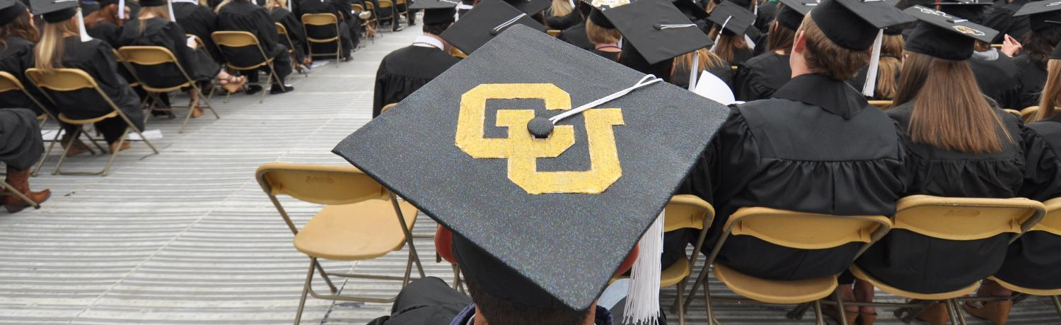 A student wearing a cap that says CU at the commencement ceremony