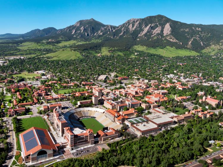 An aerial view of CU Boulder's main campus with the Flatirons beyond