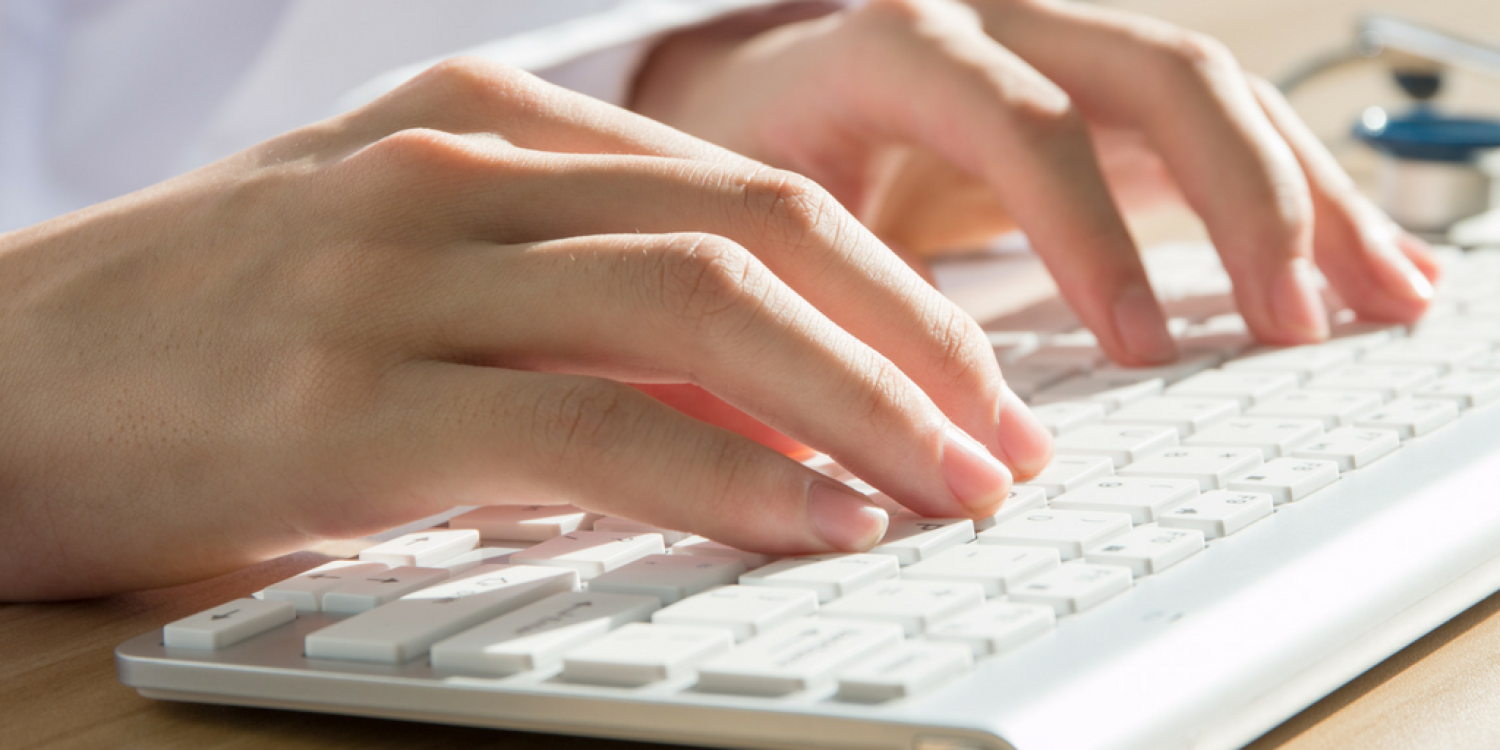 Two hands typing on a keyboard