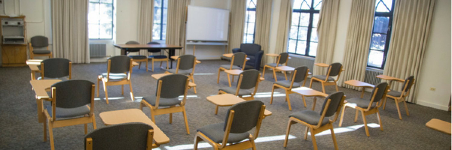 Residence hall classroom with a lot of windows, chairs with desks attached, carpet