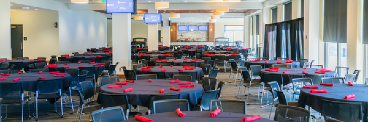 Conference room in Folsom Stadium with round, set tables, ready for a conference dinner