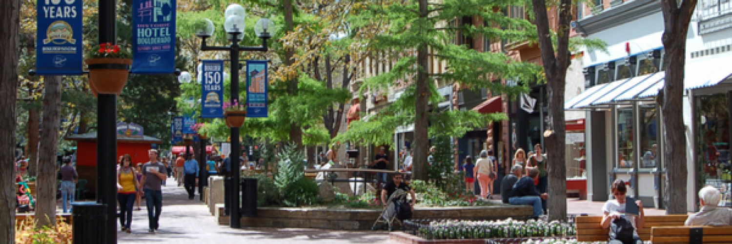 Pearl Street pedestrian mall with shops lining the street, benches, flower beds, trees, people walking and sitting on benches