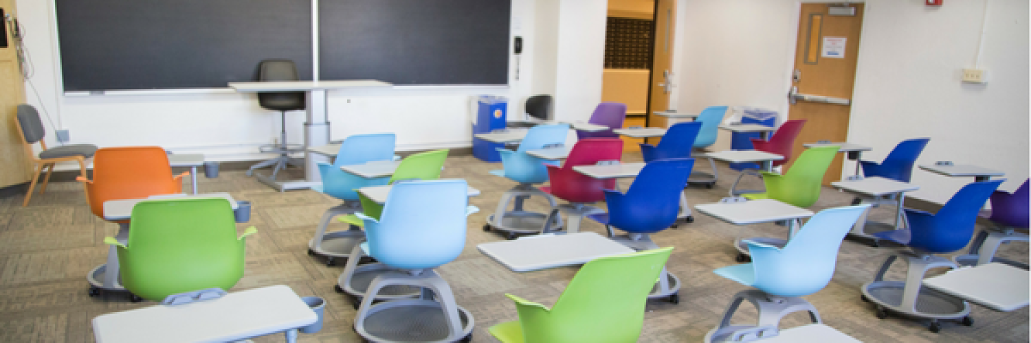 Residence hall classroom with colorful chairs with desks attached facing the chalkboard