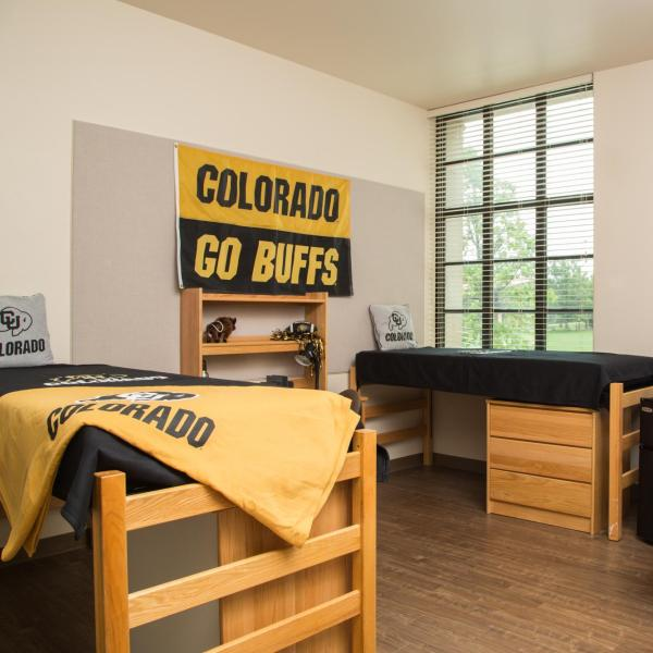 Double res hall room with two beds, desks, chairs, microfridge, window