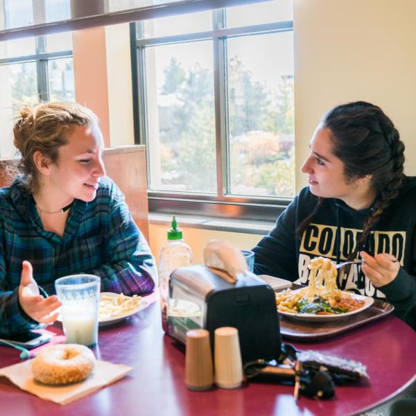 Two female students sitting at a table and eating lunch in the C4C dining center