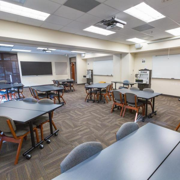 Large residence hall classroom in Will Vill North with move-able tables, windows, chalkboard