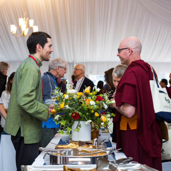 Two men talking over a flower arrangement on a catering table