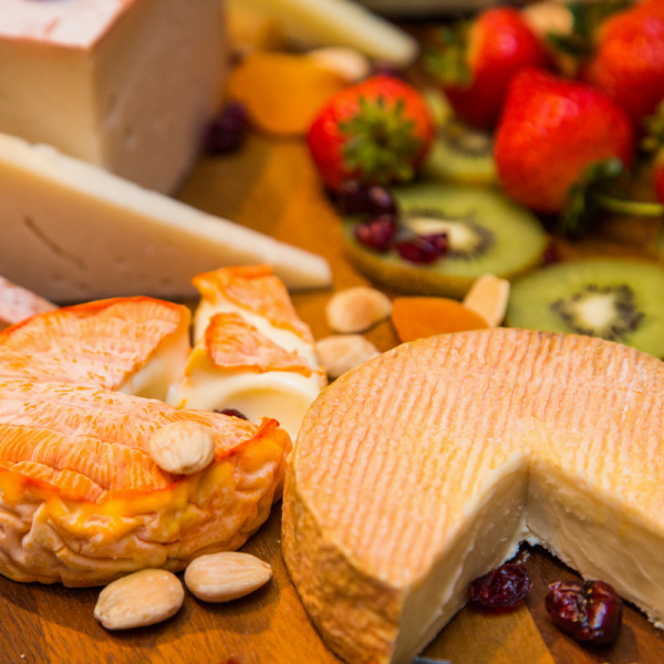 Several cheeses and fruits on wood board