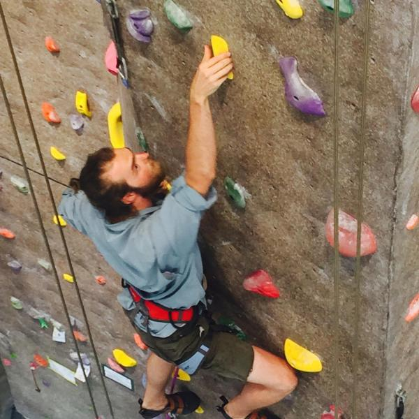 Guy climbing inside climbing wall at CU rec center