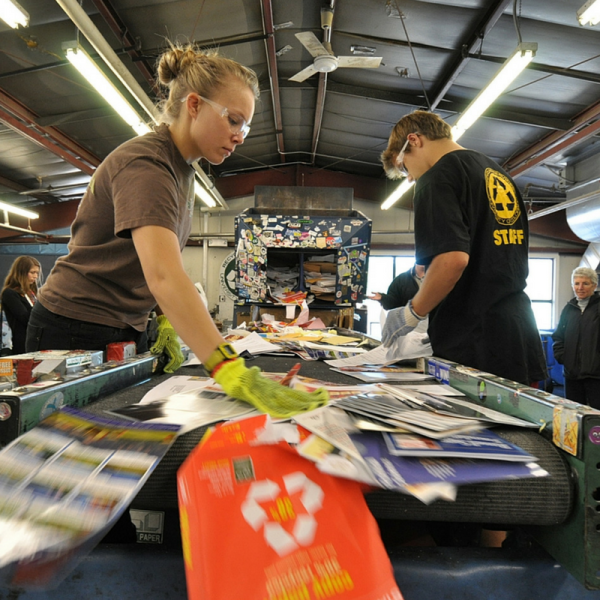 Two student staff members sorting recycled materials