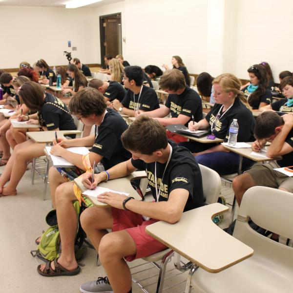 Camp attendees taking notes at desks in academic classroom