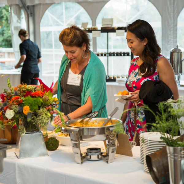 Two women selecting food on a buffet