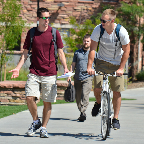 Two guys, one walking one cycling, talking