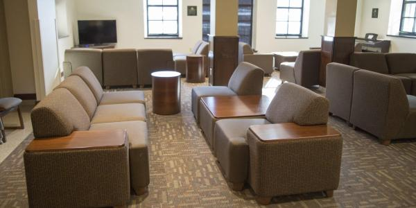 Baker lounge area with modular furniture, round side tables, carpeted floors, windows, tv