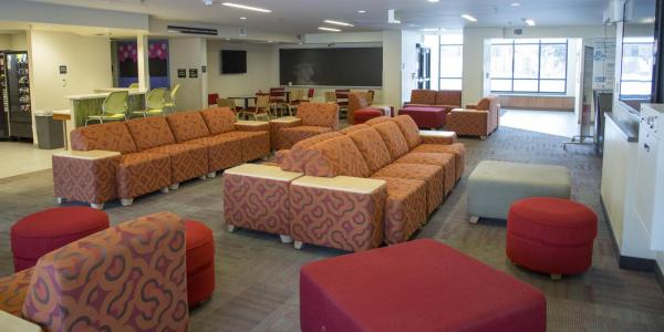 Kittredge West lounge area with multi-patterned modular furniture and foot stools, windows, carpeted floors