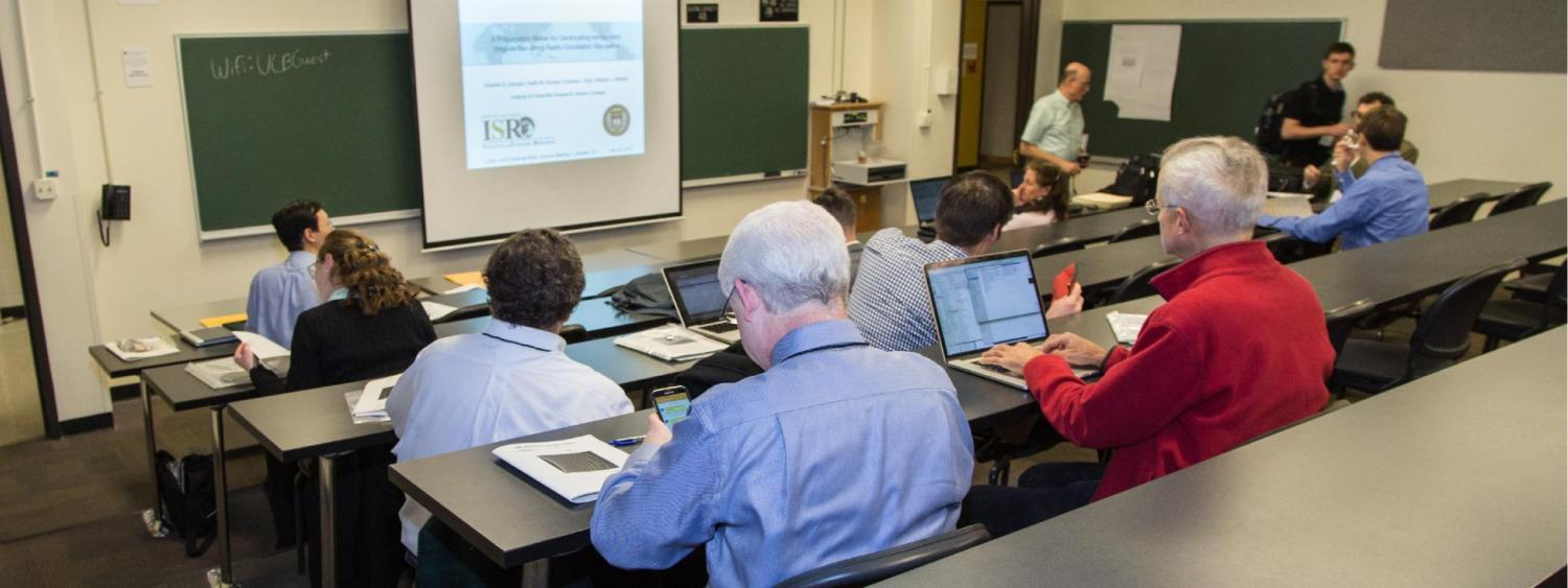 Attendees sitting in an academic classroom participating in a lecture