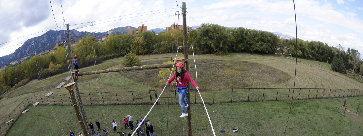 Conference attendee walking on a rope on a ropes course