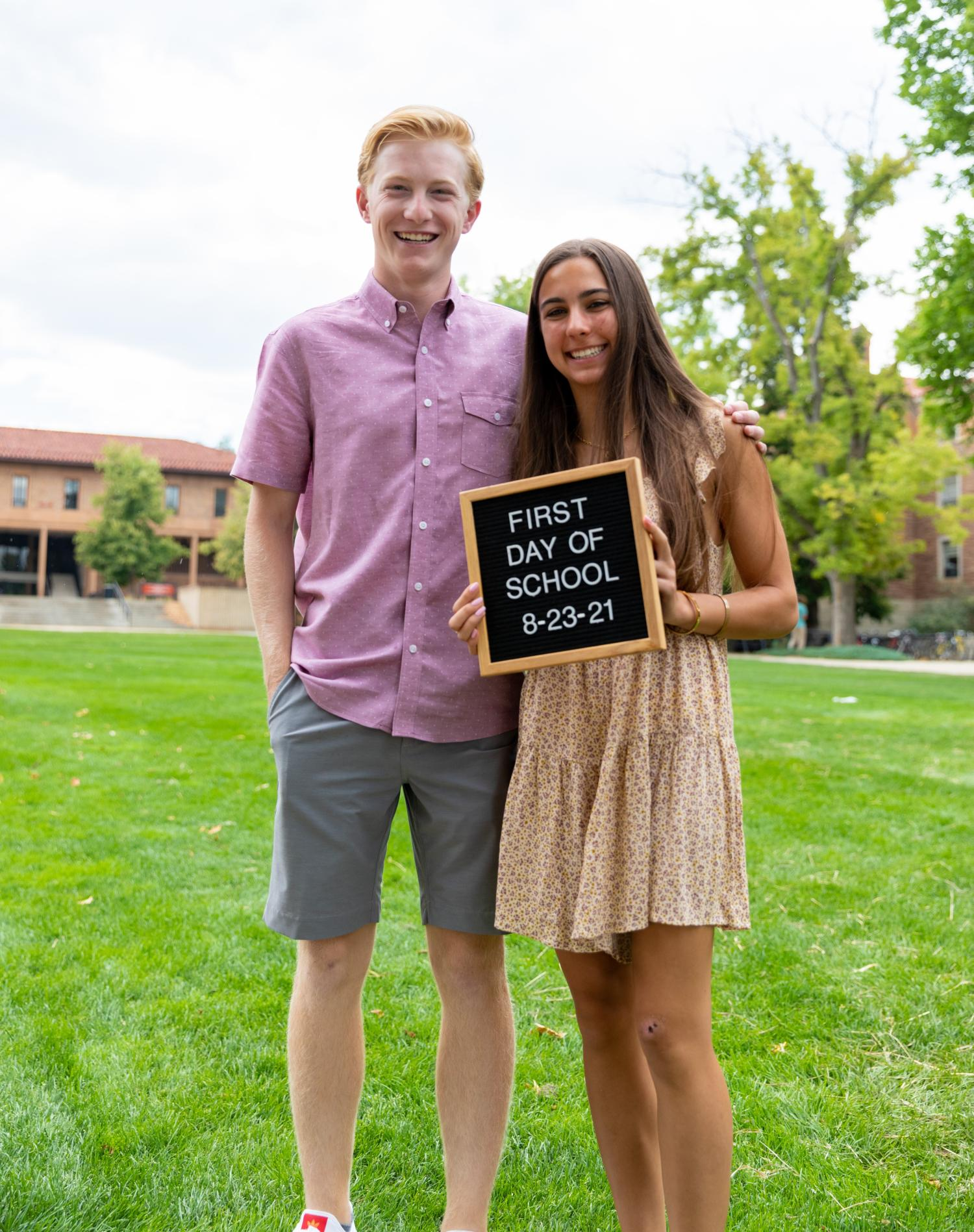"""two students smiling with a sign that reads """"first day of school august 23, 2021"""""""