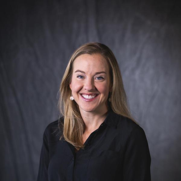 blonde woman in black top smiling