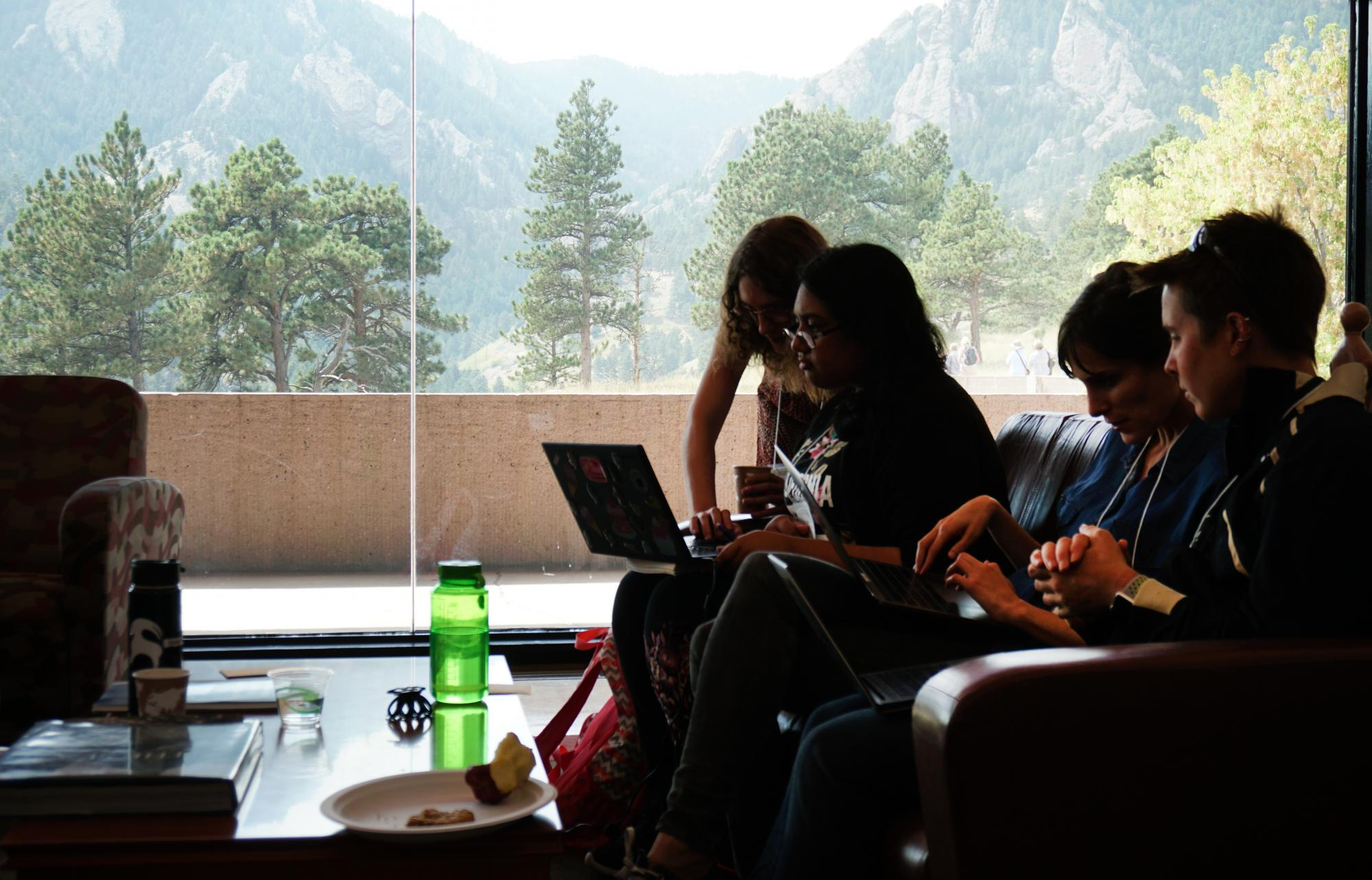 Four hackathon participants discuss their work, with Boulder's Flatirons in the background.