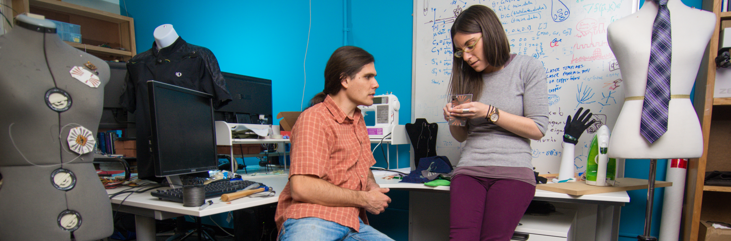 Two graduate students discuss their wearable technology research in the lab.