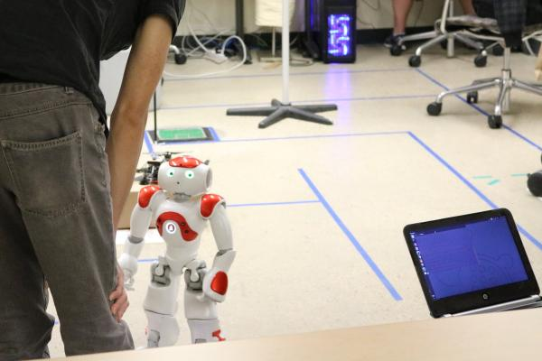 Graduate student interacting with artificially intelligent robot