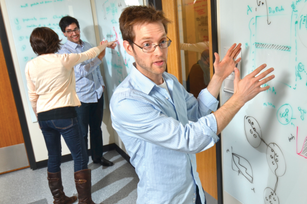 Professor explaining concepts and theories in computing on a whiteboard