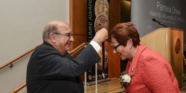 Chancellor Phil DiStefano hangs the Norlin medal around Pam Drew's neck.