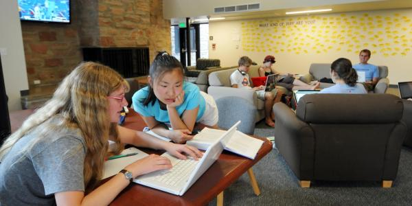 Two students work on a project in the common area of Andrews Hall