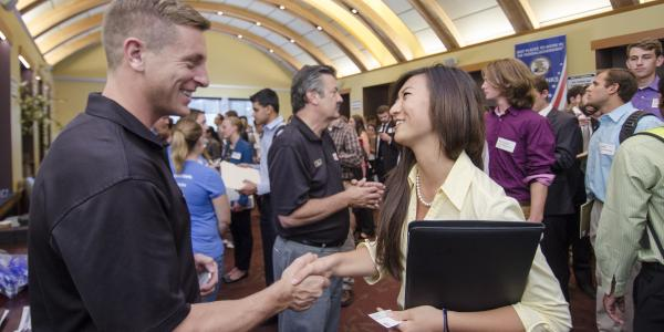 A student meets an employer at a campus career fair.