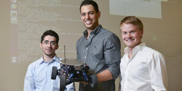 Chris Heckman (right) and two graduate students hold their Ninja Car in their autonomous vehicle lab.