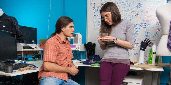 Two graduate students discuss a project in their wearable technology lab