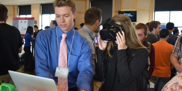 A student demonstrates his senior project for a visitor wearing a virtual reality headset at the 2016 CS Expo.