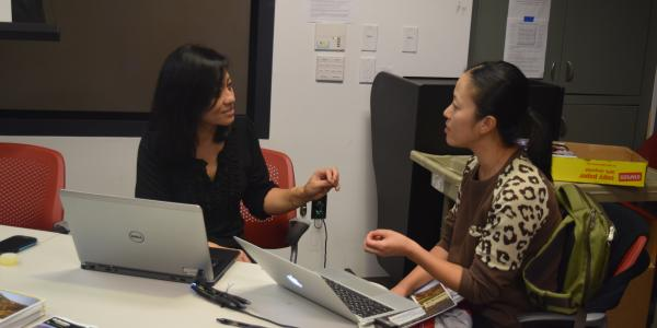 Advisor Rajshree Shrestha speaks with a prospective graduate student.