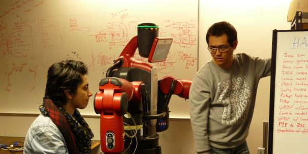 Two students discuss a robotics project in a lab