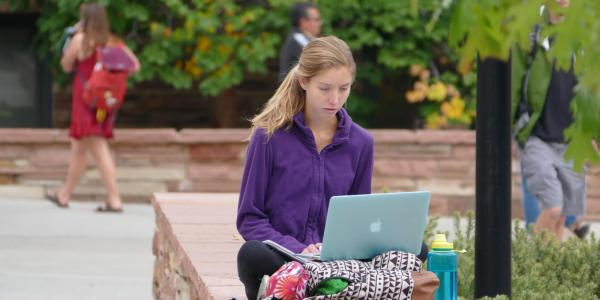 A student working on a laptop on an outdoor bench.