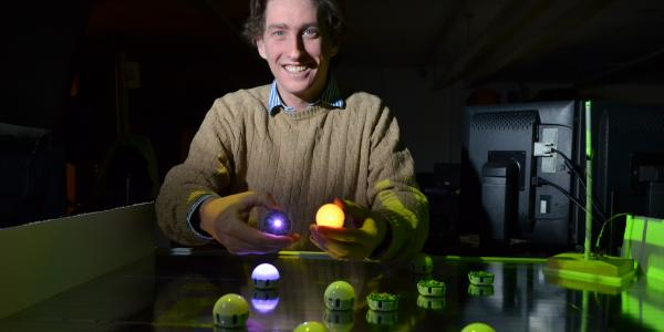Assistant Professor Nikolaus Correll demonstrates his team's swarm robots.
