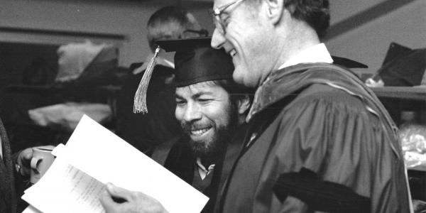 Steve Wozniak looks over the graduation program with engineering Dean Richard Seabass.