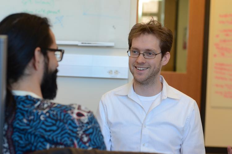 Aaron Clauset chats with a colleague