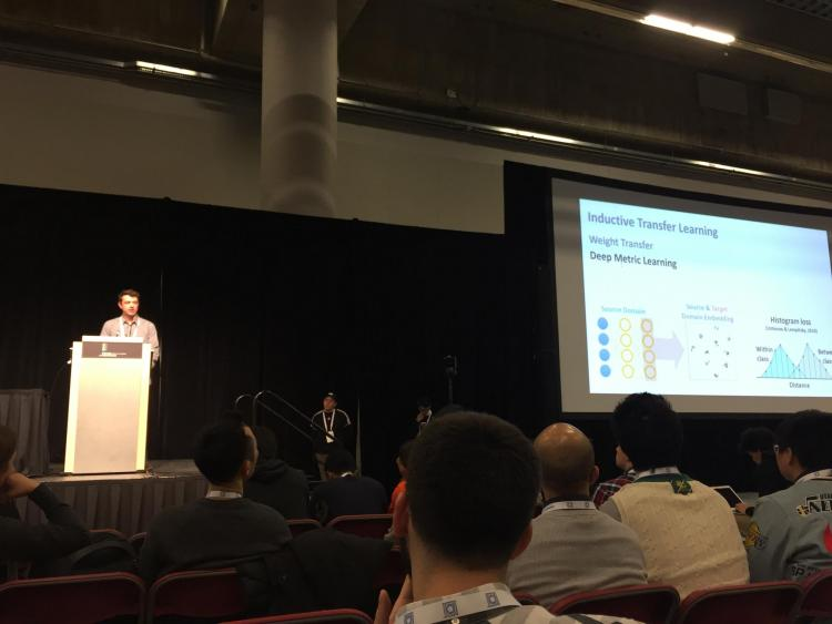 Tyler Scott on stage for his paper presentation during NeurIPS.