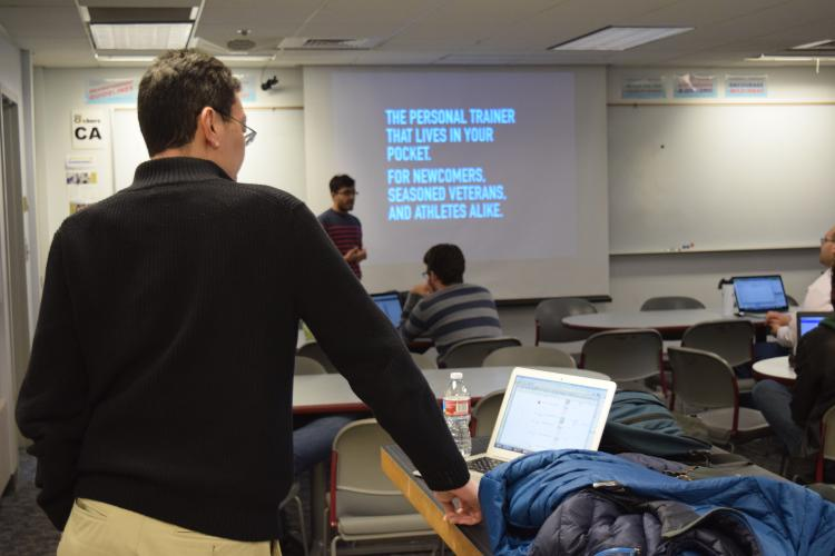 Rick Han looks on as his students practice their pitches during a class session