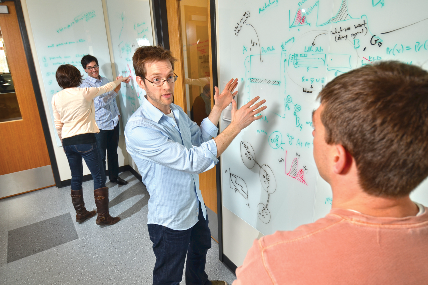 Assistant Professor Aaron Clauset and a student discuss an equation at a whiteboard.