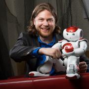 Dan Szafir fist-bumps Nao the robot.