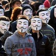Protesters wearing Guy Fawkes masks.