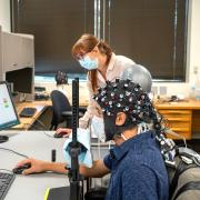 Rosy Southwell and Cooper Steputis demonstrate the use of a functional near-infrared spectroscopy device in D'Mello's lab