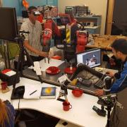 Three students experiment with human-robot interaction and autonomous manipulation in the Correll Lab.