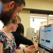 A student works on a coding project as her teacher looks on.