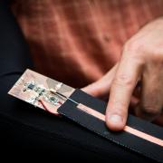 A close-up view of the wearable device being controlled with a finger swipe.